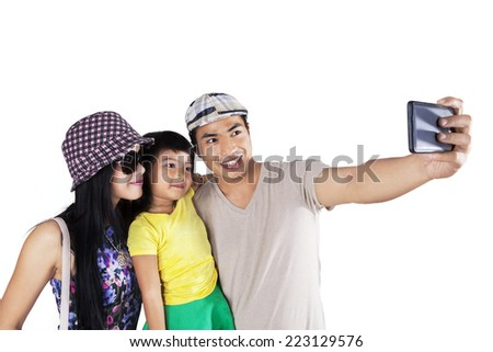 Asian family using smartphone to take self picture, isolated over white background - stock photo