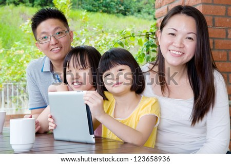 Asian family using tablet computer - stock photo