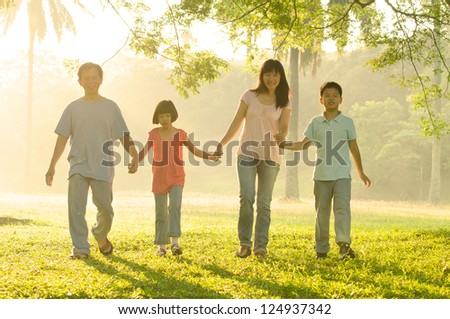 asian family walking in the park - stock photo