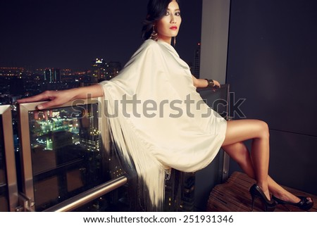 Asian fashion model in balcony with night city view on background - stock photo