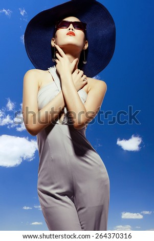 Asian fashion model in sunglasses and hat against bluse sky background - stock photo