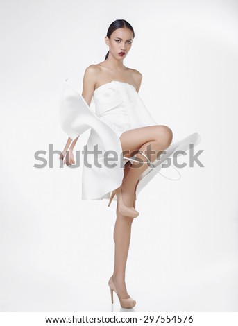 Asian fashion model in white dress in studio against white background - stock photo