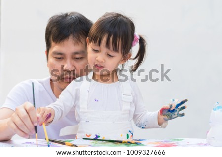 Asian father and daughter are playing by color painting together with fully happiness moment on the white background, concept of art education learning activity for kid in family lifestyle.