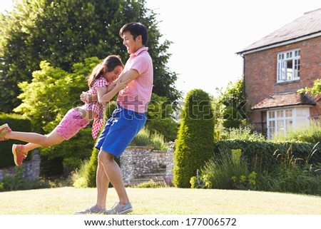 Asian Father And Daughter Playing In Summer Garden Together - stock photo