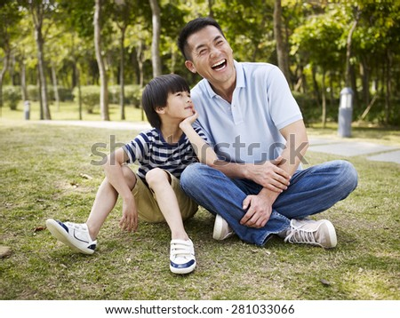 asian father and elementary-age son sitting on grass outdoors having an interesting conversation. - stock photo