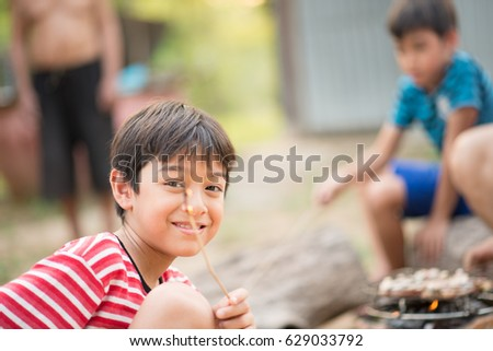 Asian Father and son making barbecue together outdoor activity