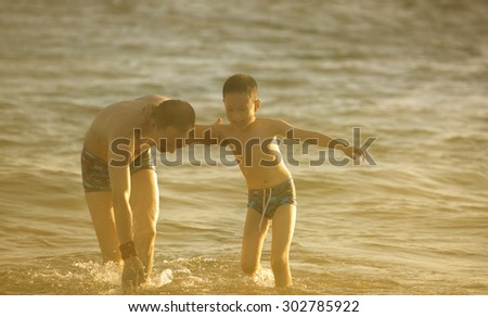 Asian father and son playing in the sea  at sunset