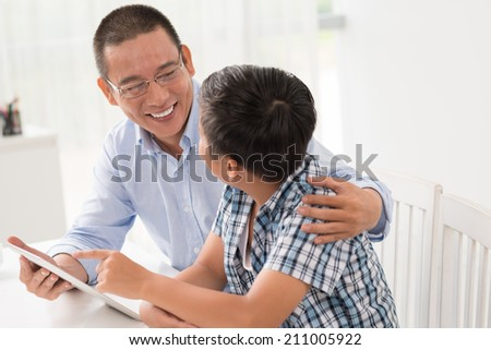 Asian father and son talking and using digital tablet - stock photo