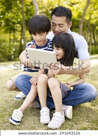 asian father and two children sitting on grass looking at tablet computer, outdoor in a park. - stock photo