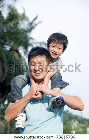 Asian father giving piggyback ride to his son in the evening sunshine