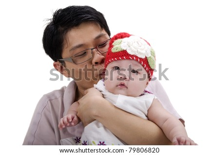Asian father kissing his baby girl - stock photo