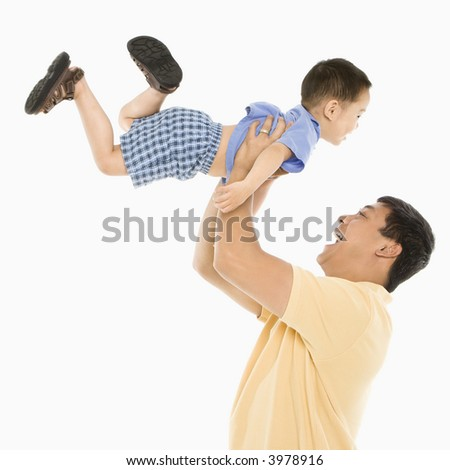 Asian father lifting son up into air in front of white background. - stock photo