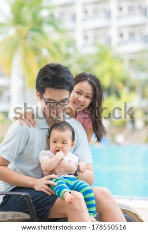 asian father , mother and daughter having holiday on a pool