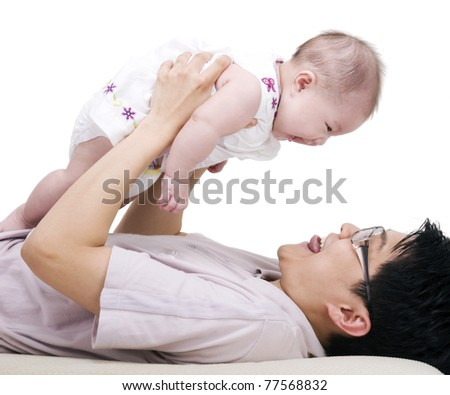 Asian father picking up his 4 months old daughter - stock photo