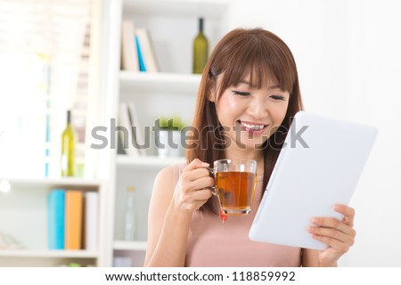 Asian female enjoying cup of tea looking at digital tablet computer inside house - stock photo