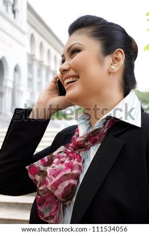 Asian Female Executive Using Mobile Phone and Smile - stock photo