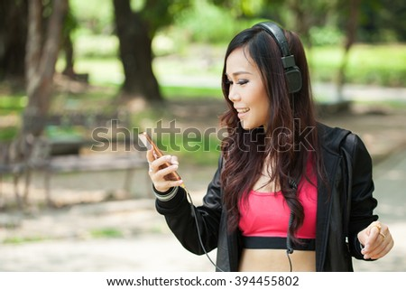 Asian female jogger listening to music in the outdoor park