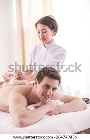Asian female masseur doing massage on male body with spa herbal balls in the spa salon.