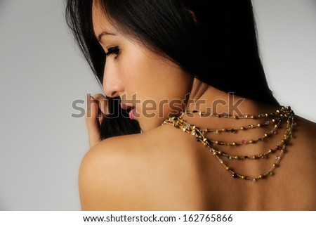 Asian female model with golden necklace - stock photo