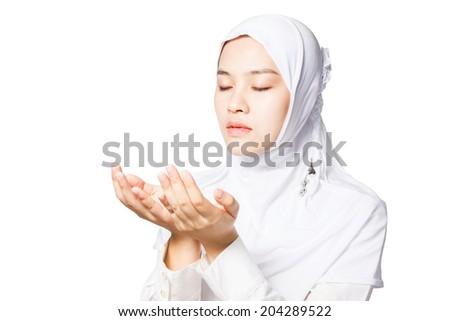 Asian female muslim wearing white dress praying isolated on white background. - stock photo