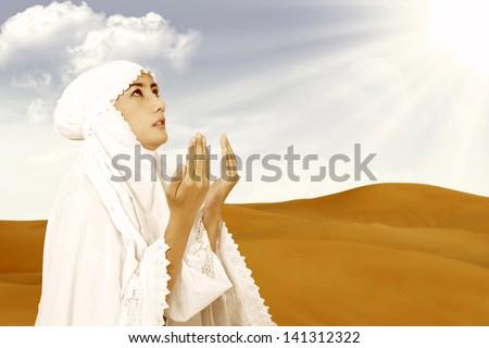 Asian female muslim wearing white dress praying on desert - stock photo