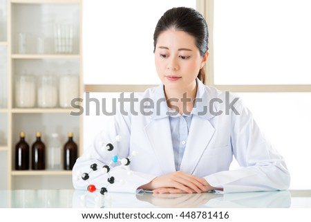 asian female scientist holding and looking at molecular model doing the Science research for human longevity Antidote - stock photo