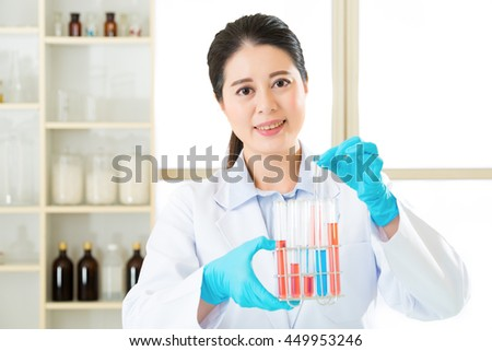 Asian female scientist researcher observing indicator color shift in laboratory - stock photo