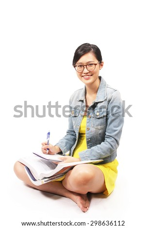 Asian female student sitting down with textbooks - stock photo