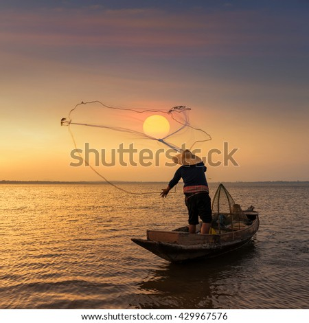 Asian fisherman on wooden boat throwing a net for catching freshwater fish in nature river in the early during sunrise time - stock photo