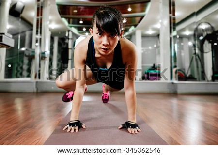asian fitness girl instructor stretching and shaping in gym - stock photo