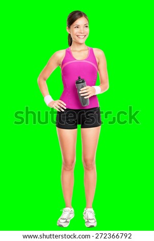 Asian fitness woman model standing in sporty gym clothing smiling happy holding water bottle. Fit young multiracial Asian Caucasian female fitness model isolated cutout on green chroma key background.