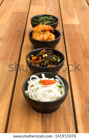Asian food composed with four black bowls with shrimps, rice noodles, kale (green cabbage) and fried vegetables. Composition on a old styled wooden table. - stock photo