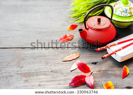 Asian food concept, tea pot, herbs and chopsticks on old wooden table - stock photo