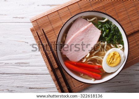 Asian Food: Ramen noodles in broth with pork, vegetables and egg in a bowl close up. Horizontal top view - stock photo