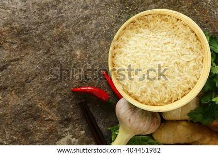 Asian food - rice, ginger, chili pepper on a stone background - stock photo