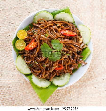 Asian food spicy fried noodles, ready to serve on dining table. - stock photo