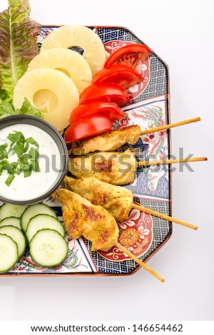 Asian food with chicken skewers, sauce, tomatoes, cucumber, pineapples and salad. - stock photo