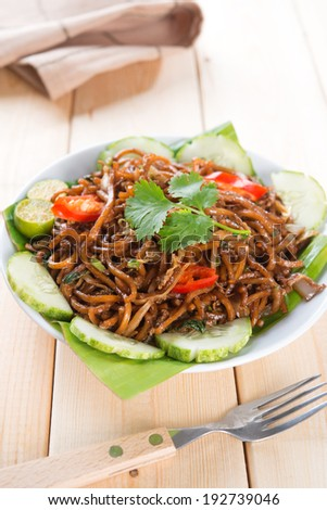 Asian fried noodles, ready to serve on dining table. - stock photo