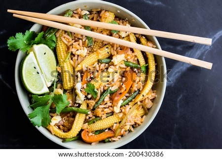 Asian fried rice with egg, vegetables, mini corn, peppers, green beans, delicious Chinese dinner - stock photo