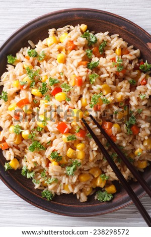Asian fried rice with eggs, corn and parsley close-up on a plate, vertical top view  - stock photo
