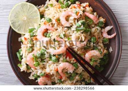 Asian fried rice with seafood, eggs, and vegetables on a plate closeup, horizontal view from above  - stock photo