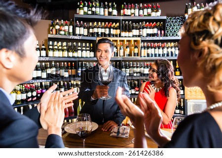 Asian friends celebrating with wine  - stock photo
