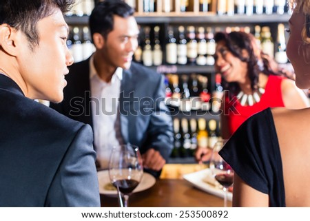 Asian friends eating in restaurant - stock photo
