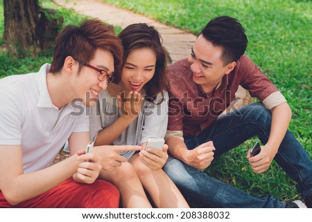 Asian friends sitting on the ground and sharing something funny in the phone - stock photo