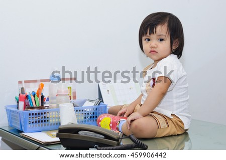 Asian  girl baby seating on work desk.(Soft focus.)