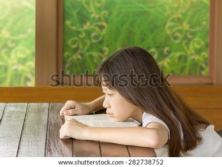 Asian girl bored learning while sitting at desk - stock photo