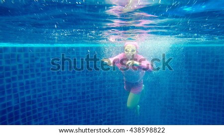 Asian Girl Diving in Swimming Pool - stock photo