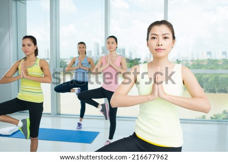 Asian girl doing yoga position during aerobics class - stock photo