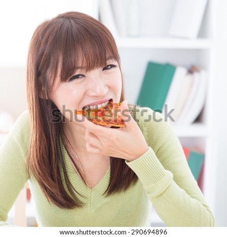 Asian girl eating pizza at home. Female living lifestyle indoors. - stock photo