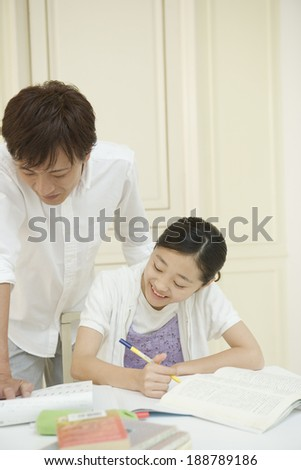 Asian girl getting taught by father - stock photo
